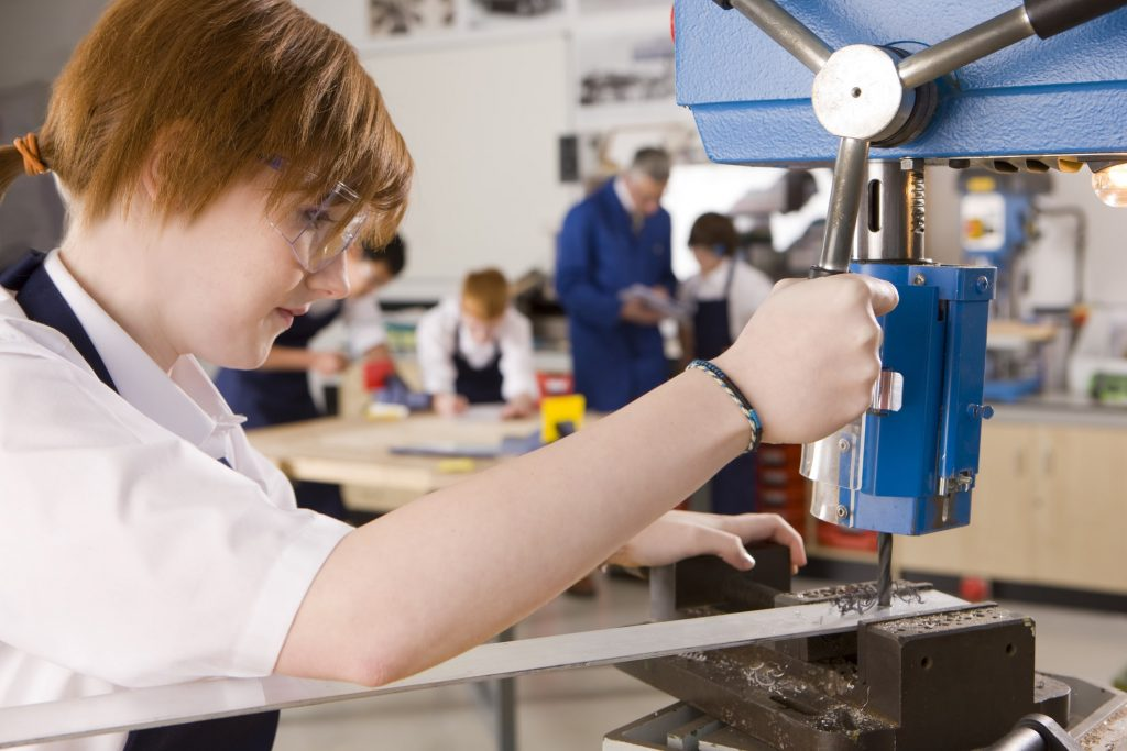Engineering student using drill in metalwork class